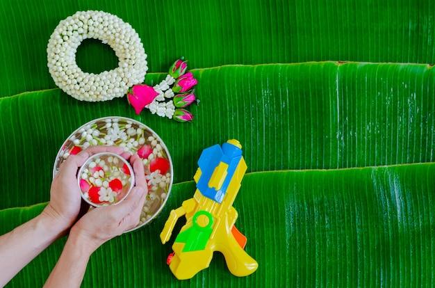 Hand hält wasserschale mit blumen zum segen, die wasserpistole und jasmingirlande auf nassem bananenblatt setzen lassen