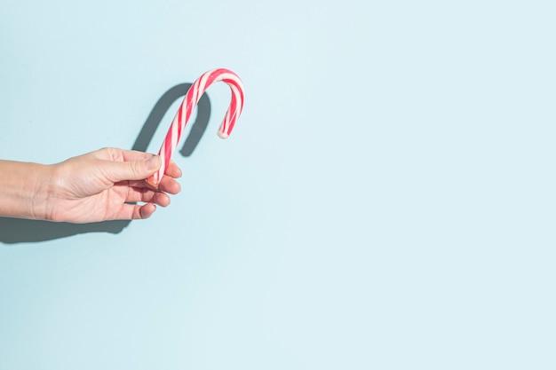 Hand hält weihnachtssüßigkeit auf blauem hintergrund. sonnenlicht.