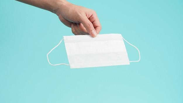 Hand hält weiße chirurgische gesichtsmaske oder einwegmaske auf mintgrünem oder tiffanyblauem hintergrund.