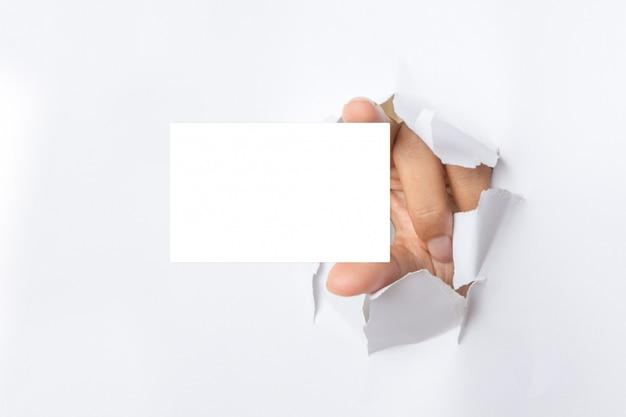 Hand hält weiße karte durch weißen heftigen papierhintergrund