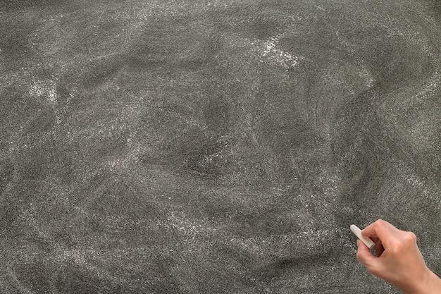 Hand hält weiße kreide und beginnt zu schreiben