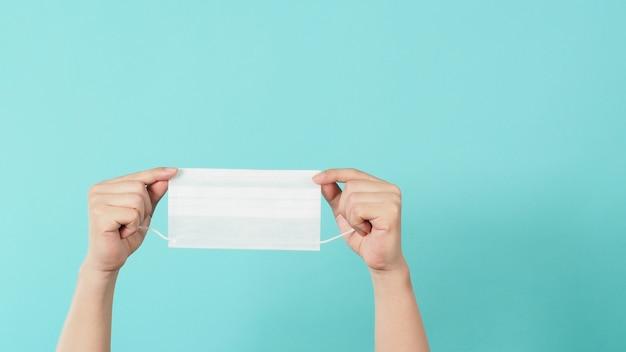 Hand hält weiße medizinische gesichtsmaske auf mintgrünem oder tiffanyblauem hintergrund.