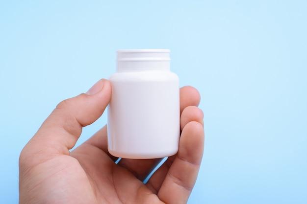 Hand hält weiße plastikflasche