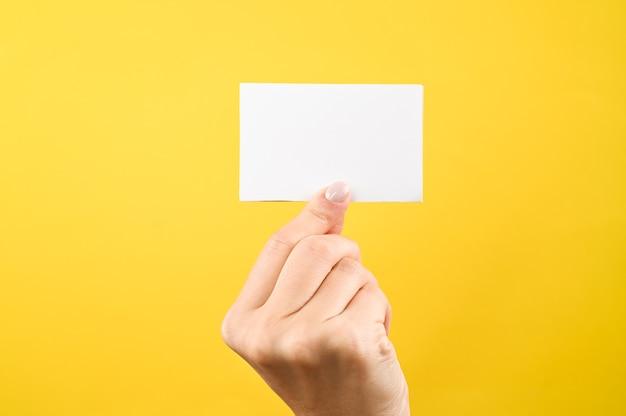 Hand hält weißes leeres zeichen auf gelbem hintergrund.