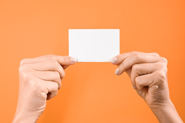 Hand hält weißes leeres zeichen auf orange hintergrund.