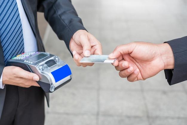 Hand hält zahlende kreditkarte mit geschäftsmann unter verwendung des zahlungsterminals
