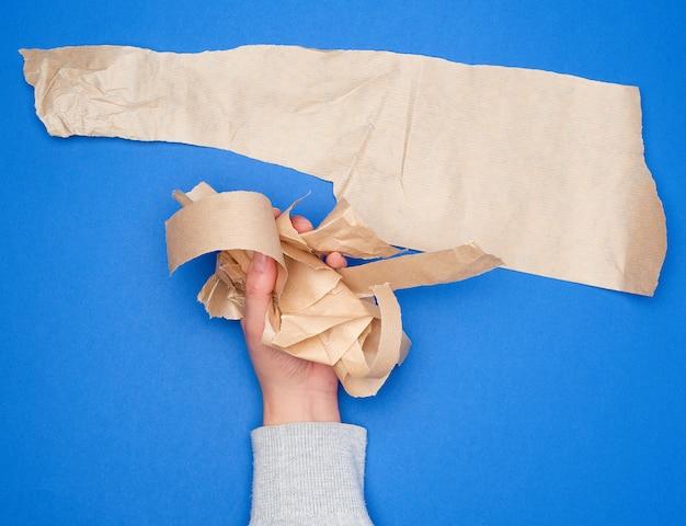 Hand hält zerknitterte stücke braunes pergamentpapier