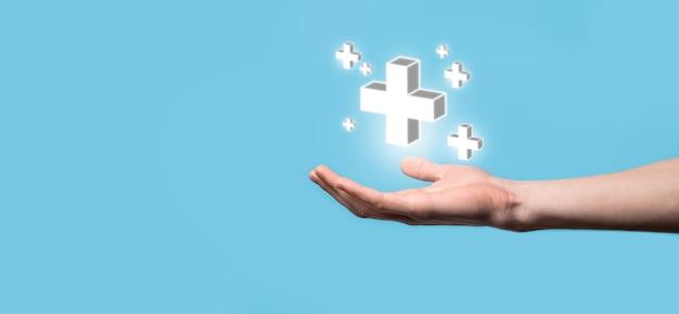 Hand halten 3d plus-symbol, mann in der hand halten bietet positive dinge wie gewinn, vorteile, entwicklung, csr, dargestellt durch pluszeichen. die hand zeigt das pluszeichen.