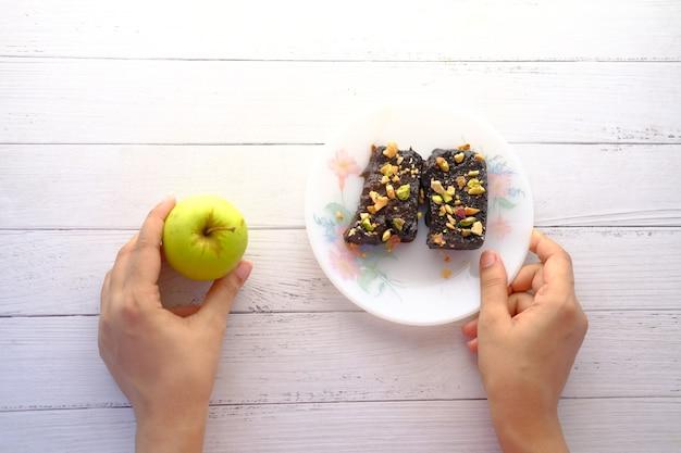 Hand halten apfel und brownie auf dem teller auf dem tisch