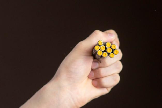 Hand halten cracker hautnah und feuer es auf dunklem hintergrund isoliert f