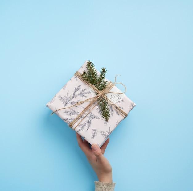 Hand halten einen geschlossenen papierkasten auf einer blauen oberfläche