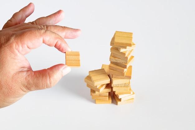 Hand halten einen holzwürfel-spielzeugstapel zum turm.