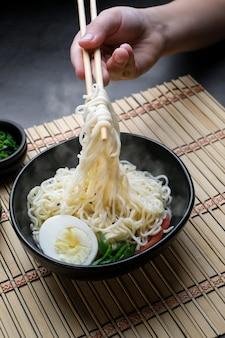 Hand halten essstäbchen-nudeln mit dampf auf schwarzem hintergrund asiatisches nudel-junk-food-konzept