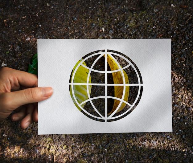 Hand halten globe paper carving mit blättern hintergrund