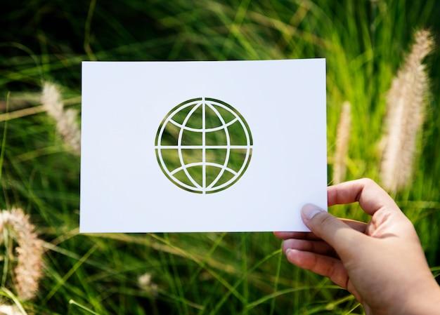 Hand halten globe paper carving mit gras hintergrund