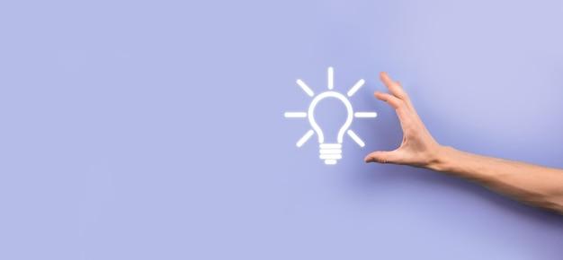 Hand halten glühbirne. hält ein leuchtendes ideensymbol in der hand. mit platz für text.das konzept der geschäftsidee.innovation, brainstorming, inspiration und lösungskonzepte