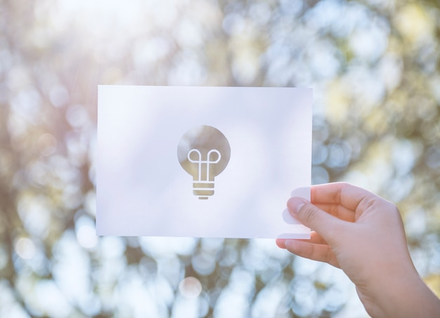 Hand halten glühbirne papierschnitzen mit der natur