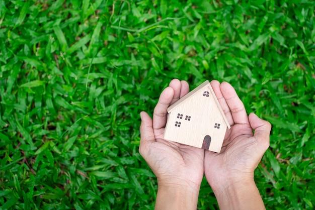 Hand halten hausmodell auf grünem grashintergrund und geschäftsinvestitionen für immobilienkonzept