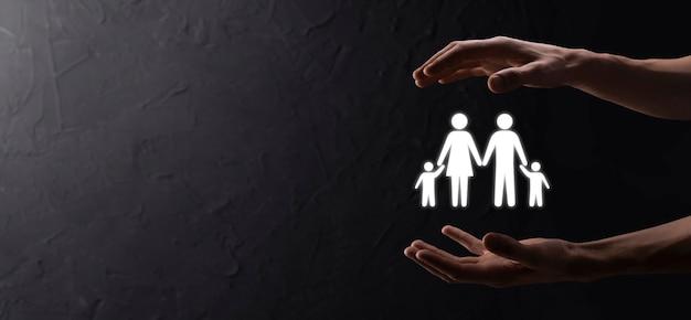 Hand halten junge familienikone. familienlebensversicherung, unterstützung und dienstleistungen, familienpolitik und unterstützung von familienkonzepten. glückliches familienkonzept. platz kopieren. mancupped hände, die papiermannfamilie zeigen