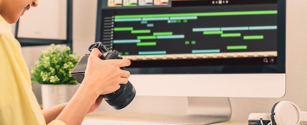 Hand halten kamera und mit anwendung video-editor arbeitet auf dem computer mit filmmaterial auf holztisch.