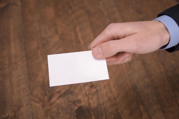 Hand halten leere weiße karte modell mit abgerundeten ecken. einfache visitenkarte modell vorlage vorlage arm halten. vorderseite der plastikkreditkarte. überprüfen sie das design der versetzten karte. business branding.