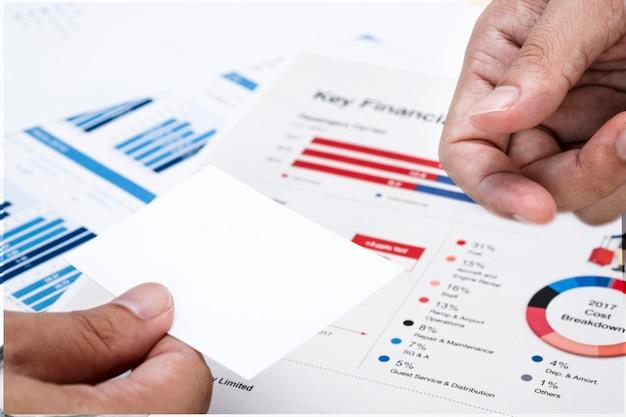 Hand halten leere weiße visitenkarte über finanzdokumenten.