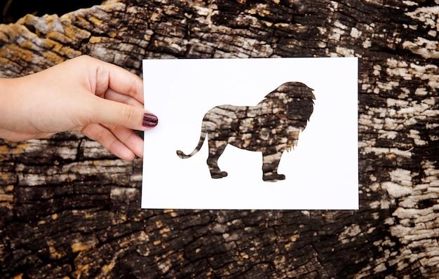 Hand halten lion paper carving mit hölzernen hintergrund