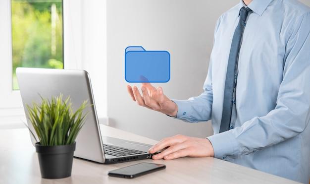 Hand halten ordnersymbol. dokumentenverwaltungssystem oder dms-setup durch einen it-berater mit einem modernen computer suchen die verwaltung von informationen und unternehmensdateien. geschäftsabwicklung