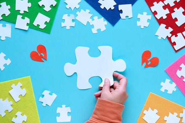 Hand halten papierpuzzle elementform. puzzle-element auf geschichteten filzstücken.