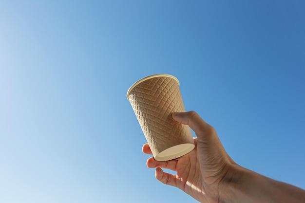 Hand halten pappbecher gegen blauen himmel hintergrund
