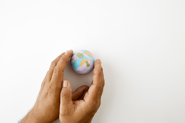 Hand halten plastilinesymbol des planeten erdekugel