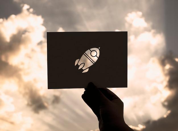 Hand halten raum-raketen-papier, das mit himmel-hintergrund schnitzt
