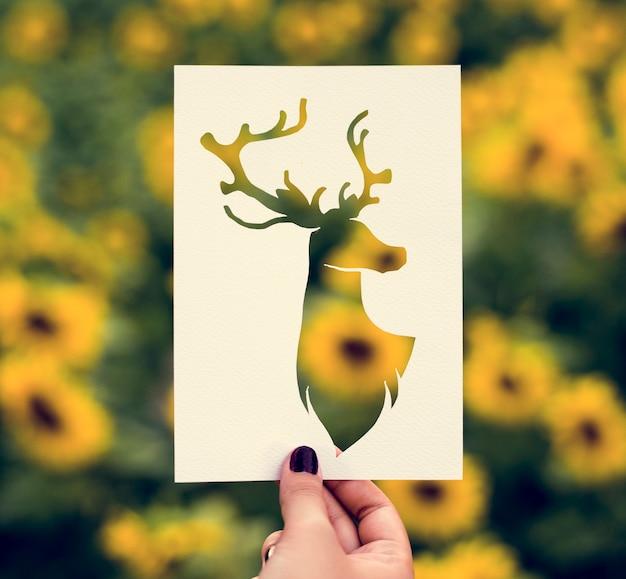 Hand halten rotwild mit dem geweih-papier, das mit sonnenblume backgro schnitzt