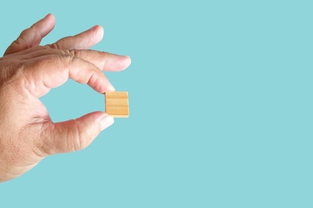Hand halten sie ein holzquadrat oder würfel mit textfreiraum