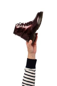 Hand halten sie einen stiefel an einem isolierten. konzept der wahl der schuhe, einkaufen, schuhreparatur