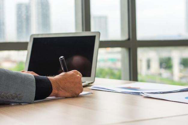 Hand halten stift schreiben auf dokument, geschäftsmann mit computer-laptop-arbeitstechnologie