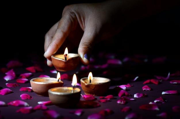 Hand halten und arrangieren laterne (diya) während diwali festival of lights
