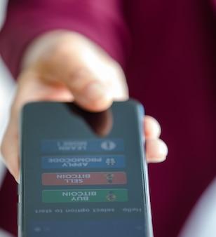 Hand halten und smartphone mit kryptowährungs-kauf- und -verkaufsknöpfen in der handelsanwendung anbieten.