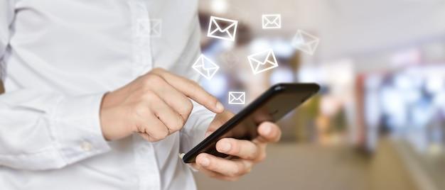 Hand halten unter verwendung des mobiltelefons mit e-mail-symbol auf dem bildschirm. konzept der geschäftskommunikationstechnologie.