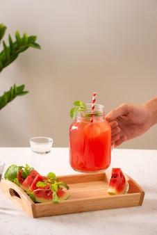 Hand halten wassermelonensaft mit wassermelonenfrucht
