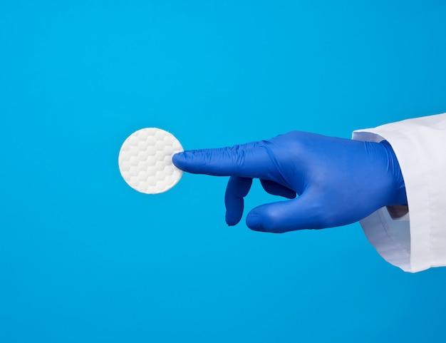 Hand halten weiße baumwolle runde scheibe für kosmetische eingriffe auf einem blauen hintergrund
