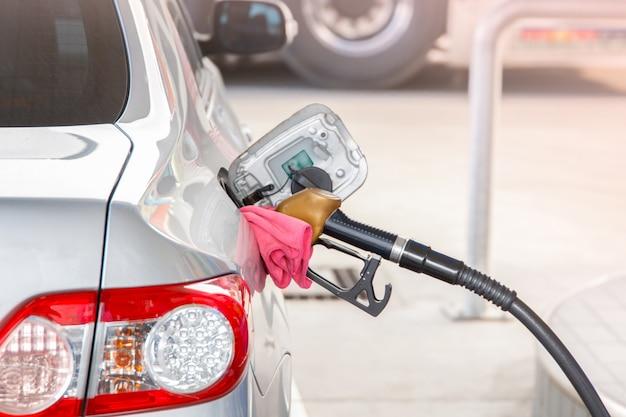 Hand halten zapfpistole, um kraftstoff im auto an der tankstelle hinzuzufügen.
