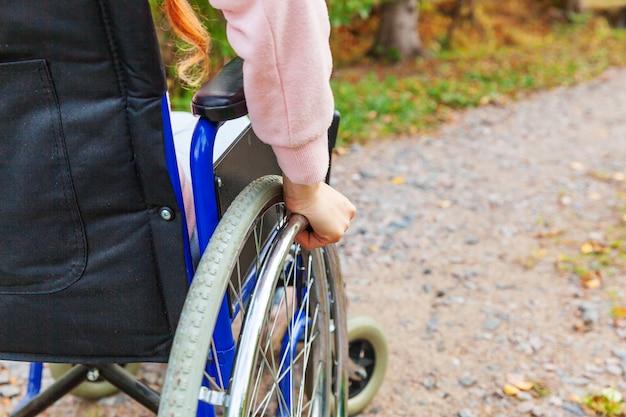 Hand-handicap-frau im rollstuhlrad auf straße im krankenhauspark, der auf patientendienste wartet. nicht erkennbares gelähmtes mädchen im ungültigen stuhl für behinderte menschen im freien. rehabilitationskonzept.