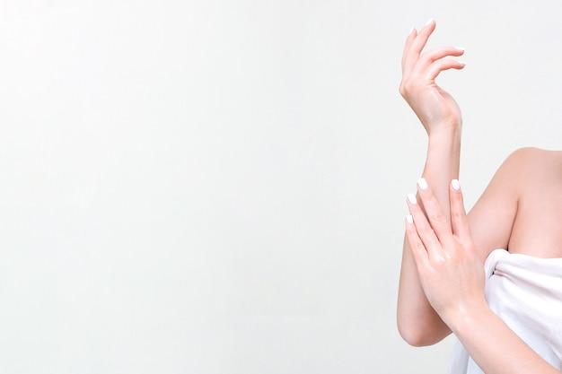 Hand haut- und körperpflege. schöne junge frau in einem handtuch berührt ihre haut