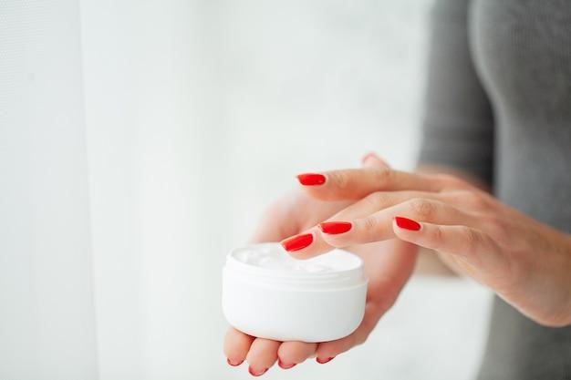 Hand hautpflege. schließen sie oben von den weiblichen händen, die cremerohr, schönheits-hände mit den natürlichen manikürenägeln halten, die kosmetische handcreme auf weicher seidiger gesunder haut auftragen