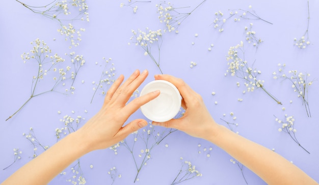 Hand hautpflegecreme in weiblichen händen, die organische naturkosmetik mit blumen anwenden