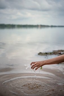 Hand heben plastikflasche vom wasser auf