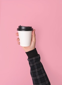 Hand holdinf kaffee pappbecher. modell für kreatives design branding kein rosa hintergrund.