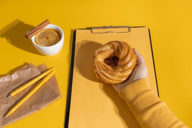 Hand holding kuchen in der nähe von tasse tee oder glühwein und lebenslauf