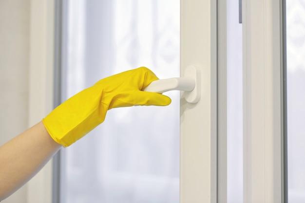 Hand im gelben gummischutzhandschuh öffnet und schließt pvc-kunststofffenster